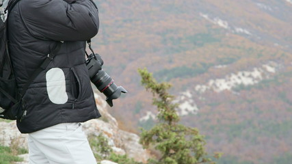 Hiking woman with camera standing on top of mountain
