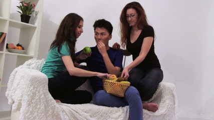 Three young people have a party and eating different fruits