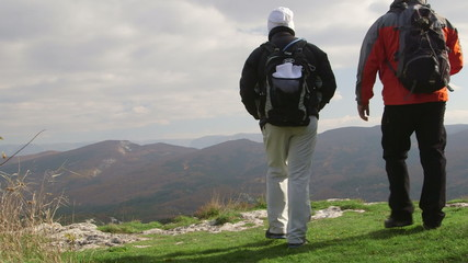 Hiking people standing with backpacks on cliff edge