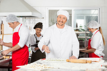 Smiling Chef Sprinkling Flour On Ravioli Pasta In Kitchen
