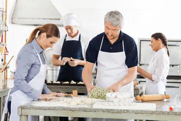 Chefs Preparing Pasta Together In Kitchen