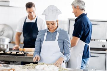 Chefs Preparing Pasta In Kitchen