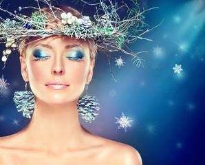 Christmas fashion model girl with snowy wreath on the head