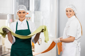 Happy Female Chefs Holding Pasta Sheets At Kitchen