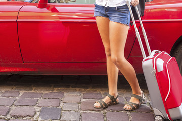 Young girl with red suitcase near the car. Travel concept.