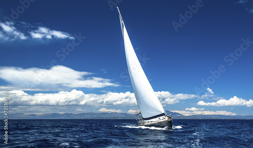 Foto Spatwand Jacht Sailing ship yachts with white sails in the open sea.