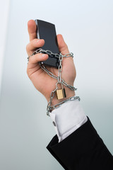 Businessman's Hand Chained With Cellphone
