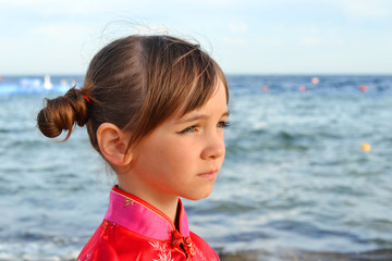 Little girl sad looks on the background of the sea