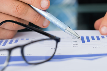 Businessman Holding Pen While Analyzing Bar Graph