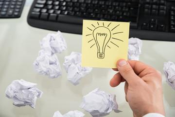 Businessman Holding Lit Bulb Drawn On Sticky Note