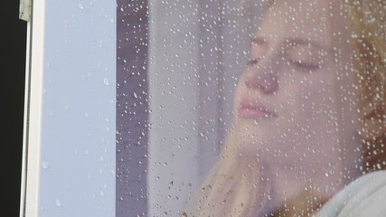 Face of sad tearful girl behind window glass with raindrops
