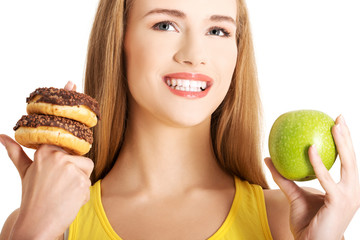Woman has a hard choice between donut and apple