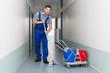 Leinwanddruck Bild - Happy Male Worker With Broom Cleaning Office Corridor