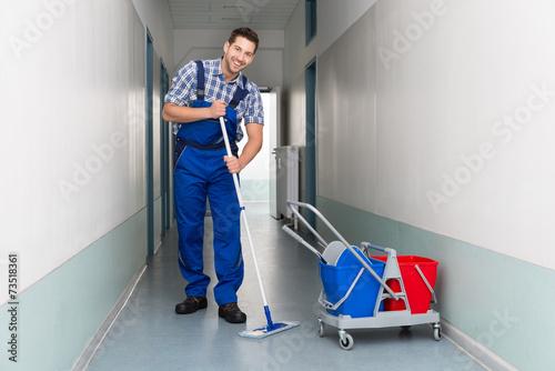 Leinwanddruck Bild Happy Male Worker With Broom Cleaning Office Corridor