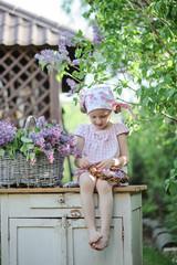 Cute little girl making lilac wreath in spring garden