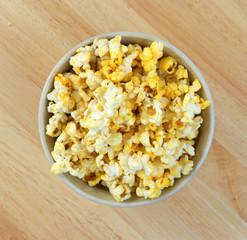Bowl full of popcorn on wood tabletop
