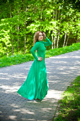 Beautiful smiling girl in a long dress in the park