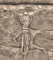 knot on a brick wall in sepia tone