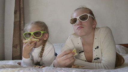 Little girl with sister eating pizza and  watching 3d TV
