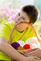 Teen boy with wicker basket and balls of yarn