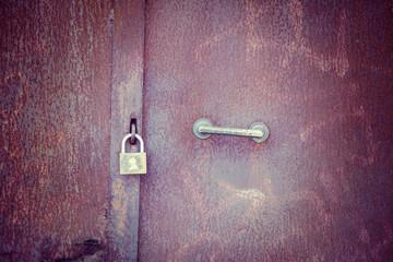 Padlock on a rusty metal door