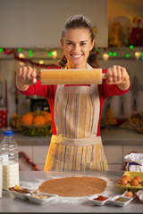 Happy young housewife showing rolling pin in kitchen