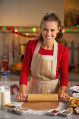 Portrait of happy young housewife making dough in kitchen