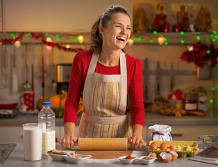 Smiling young housewife making dough in kitchen