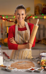Portrait of happy young housewife with rolling pin in kitchen