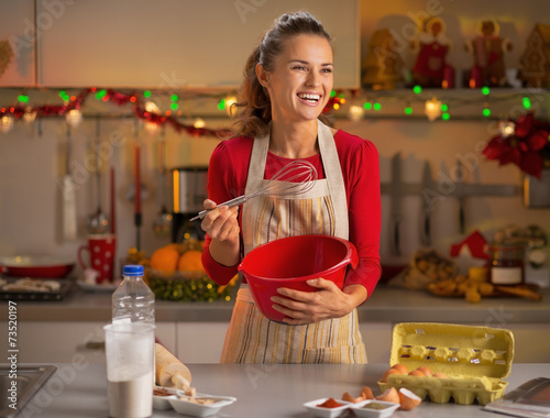 Happy young housewife whisking dough in kitchen
