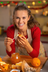Happy young housewife eating homemade orange jam