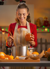 Happy young housewife making orange jam in christmas kitchen