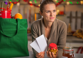 Thoughtful young housewife with christmas shopping bag