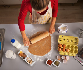 Young housewife rolling dough in kitchen