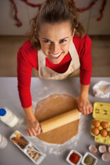 Portrait of happy young housewife rolling dough in kitchen