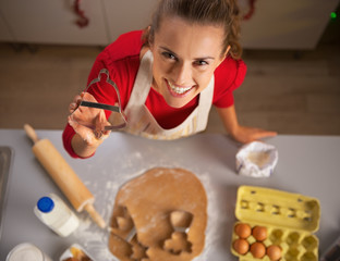 Happy young housewife showing christmas dough cutter