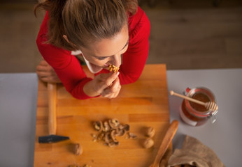Young housewife eating walnuts in kitchen