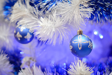 White and blue christmas glass balls on faux pine tree