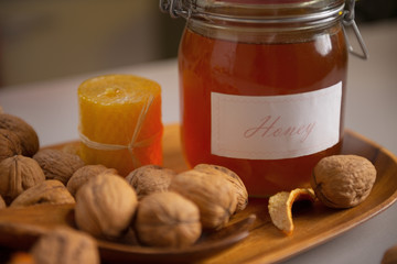 Closeup on walnuts and jar of honey on table