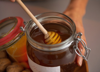 Closeup on young housewife putting honey dipper in honey jar