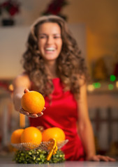 Closeup on happy young housewife giving orange