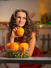 Portrait of thoughtful young housewife with plate of oranges