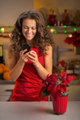Happy young housewife writing sms in christmas decorated kitchen