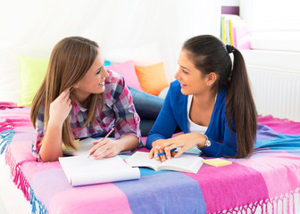 Two female students lying on bed and learning