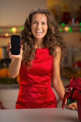 Closeup on happy young housewife showing cell phone in kitchen