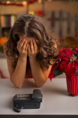 Stressed young housewife near phone in christmas kitchen