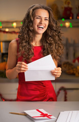 Portrait of happy young housewife with christmas letter