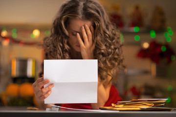 Closeup on frustrated young housewife with letter