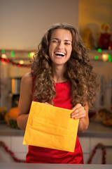 Smiling young housewife opening envelope