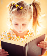 little girl reading the book